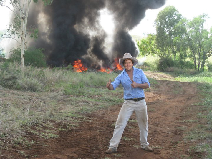 Betoota Mayor, Keith Carton, poses for a photo in front of the controlled fires that will make way for the new outback desalination plant. One of the few industries left alive after the town lost country music
