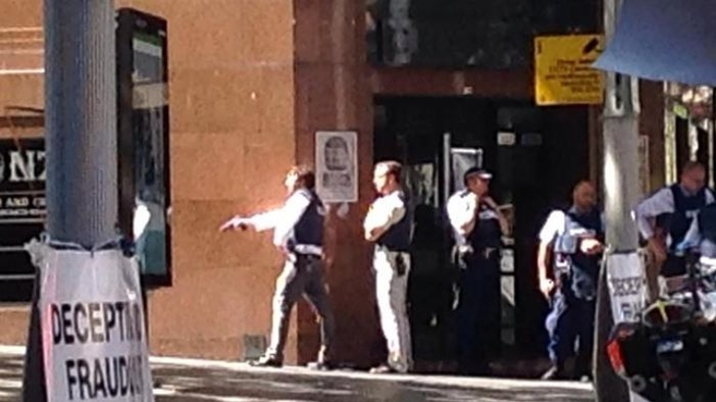 Police draw their guns outside the Lindt Chocolat Cafe in Sydney's Martin Place.