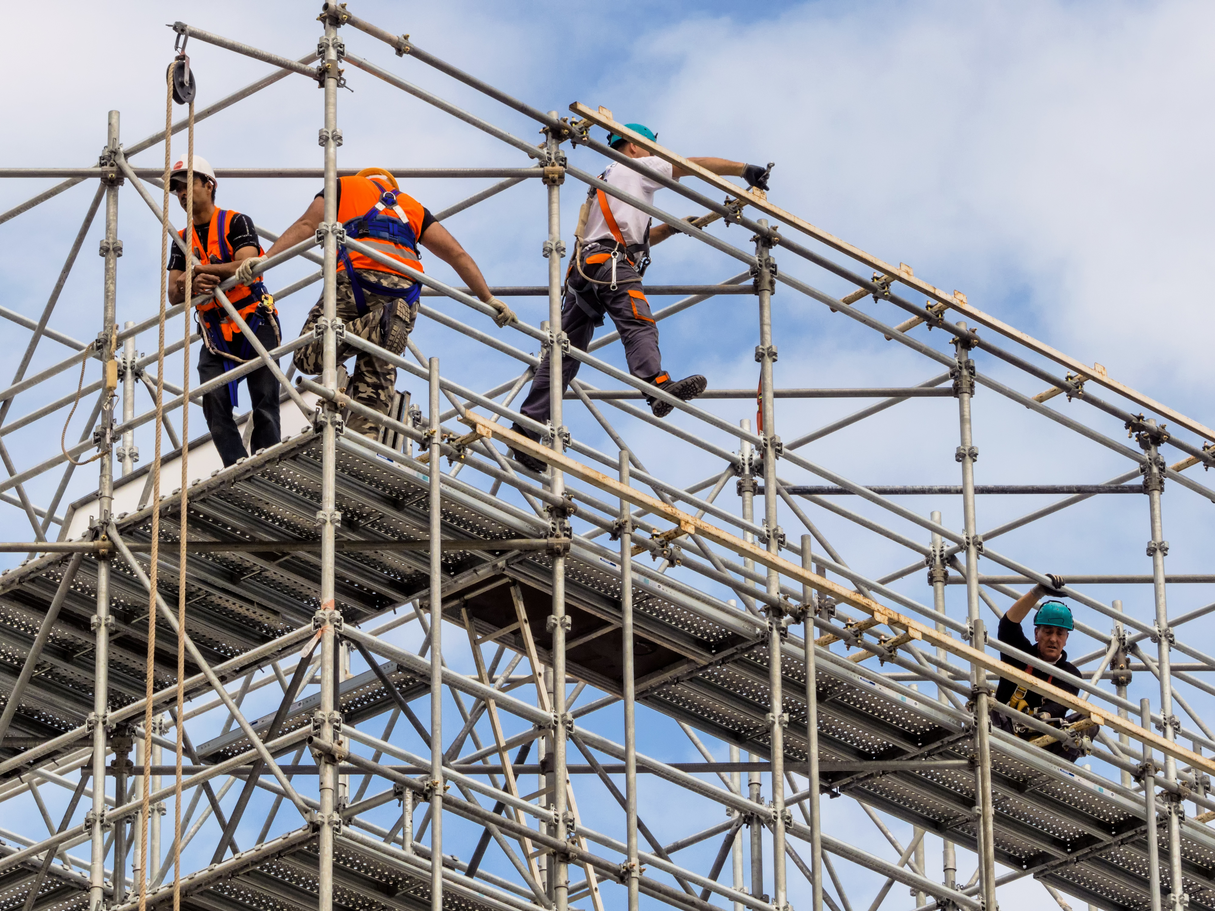 Three Pacific Islander-Australians scaffolding on the top of a Brisbane skyscraper.