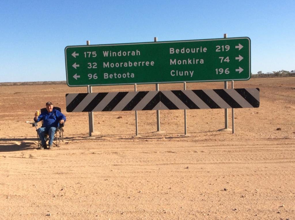 Tony Windsor poses next to a road sign, 96 kilometres from Betoota