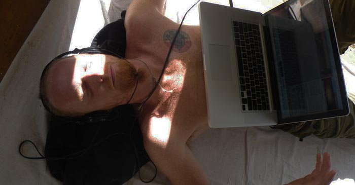 Hipster Lying In Bed With Overheating Laptop On Chest Proudly Declares He Doesn't Own A TV